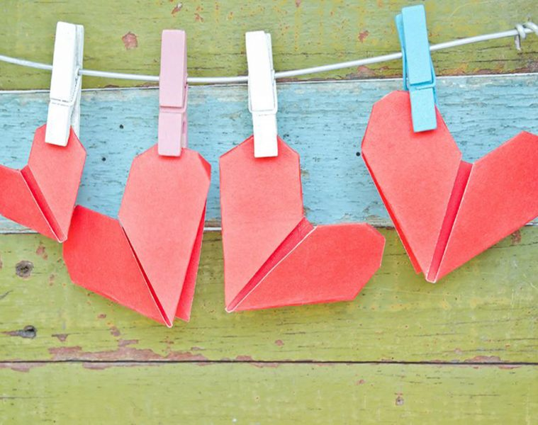 17385605 - paper heart hanging on the clothesline. on old wood background. valentines day theme .