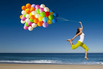 girl with balloons on beach